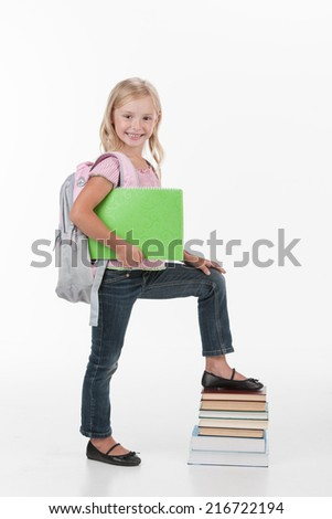 portrait of school girl holding books. cute girl standing isolated on stack of books - stock photo