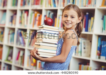 Portrait of school girl holding stack of books with apple in library at school - stock photo