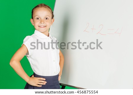 portrait of school girl in a school uniform near whiteboard. Learning, idea and school concept. Image on green background. - stock photo