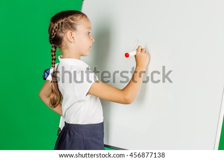 portrait of school girl in a school uniform near whiteboard with red marker. Learning, idea and school concept. Image on green background. - stock photo