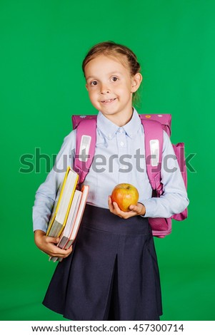 portrait of school girl in a school uniform with apple and books. Learning, idea and school concept. Image on green background. - stock photo