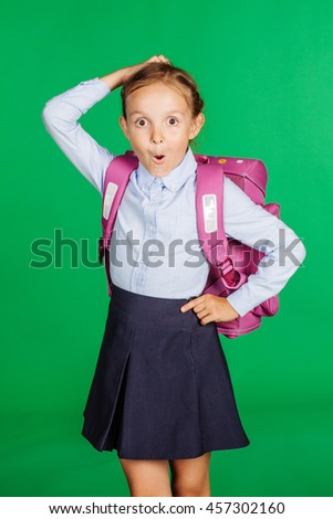 portrait of school girl in a school uniform with. Learning, idea and school concept. Image on green background. - stock photo
