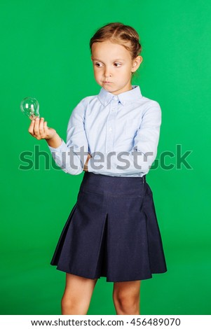 portrait of school girl in a school uniform with light bulb. Learning, idea and school concept. Image on green background. - stock photo