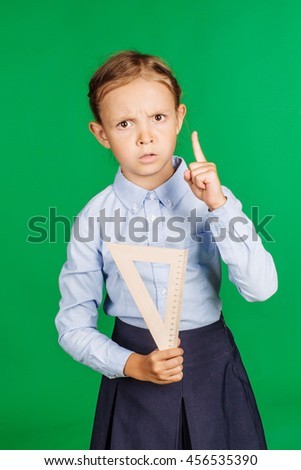 portrait of school girl in a school uniform with wood triangle ruler. Learning, idea and school concept. Image on green background. - stock photo