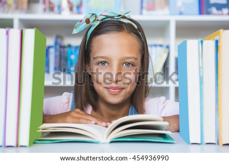 Portrait of school girl reading a book in library at school - stock photo