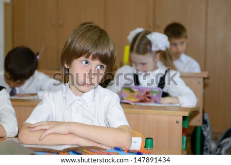 Portrait of schoolboy at workplace with another children in classroom on background - stock photo