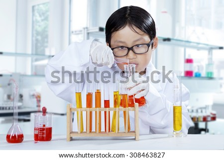 Portrait of schoolboy doing chemistry experiment while wearing coat in the laboratory