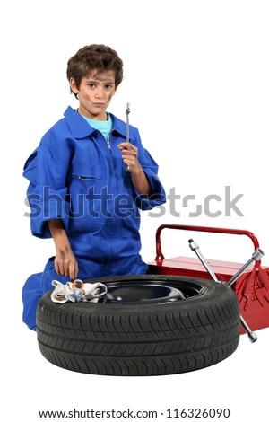 portrait of schoolboy dressed as garage mechanic - stock photo
