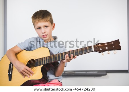 Portrait of schoolboy playing guitar in classroom at school
