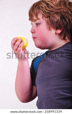 portrait of schoolchild with backpack eating apple - stock photo