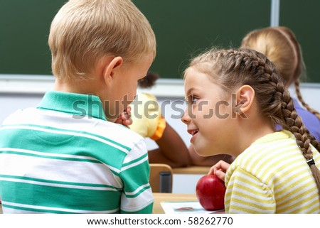 Portrait of schoolchildren sitting in classroom and chatting at lesson - stock photo