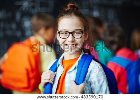 Portrait of schoolgirl in glasses smiling at camera