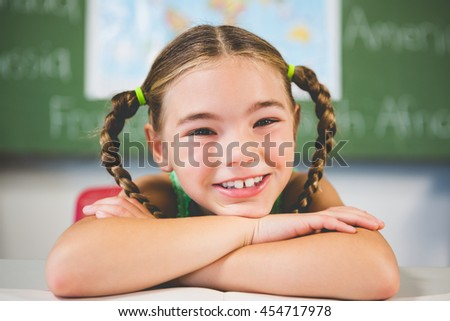 Portrait of schoolgirl leaning on a book in classroom at school - stock photo