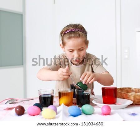 Portrait of schoolgirl painting Easter eggs - stock photo