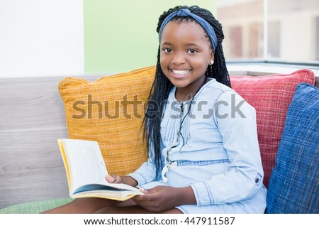 Portrait of schoolgirl sitting on sofa and reading book in library