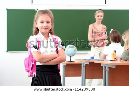portrait of schoolgirl with a school backpack, in the background a classroom and the teacher tells the class - stock photo