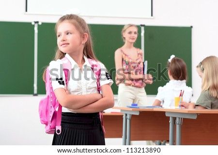 portrait of schoolgirl with a school backpack, looking out the window - stock photo