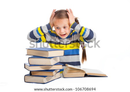 Portrait of schoolgirl with horror looking at pile of books on isolated white background