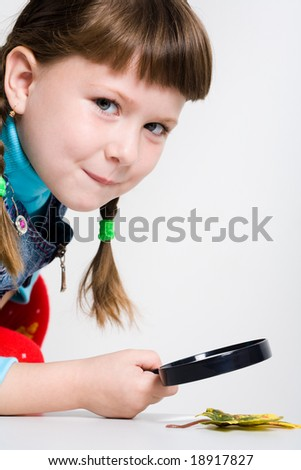 Portrait of schoolgirl with magnifying glass and autumn leaf near by - stock photo