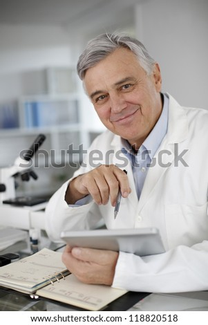 Portrait of scientist in lab using digital tablet - stock photo