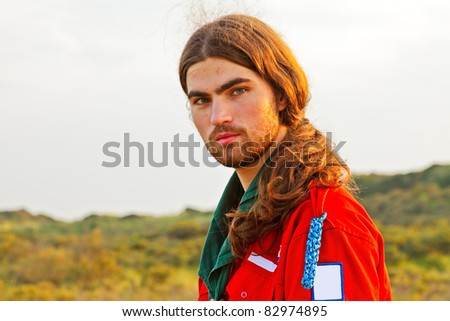 Portrait of scout young man with long hair standing in landscape of dunes - stock photo