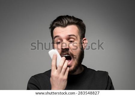 Portrait of screaming man talking on the phone on a gray background