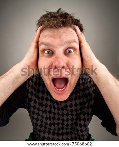Portrait of screaming surprised man holding head - stock photo