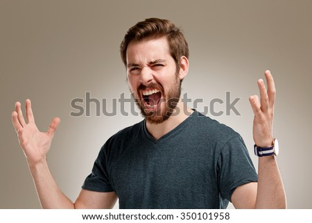 Portrait of screaming young man with beard, on neutral background