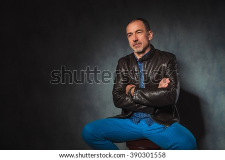 portrait of seated mature man in leather jacket posing looking away with hands crossed in gray studio background
