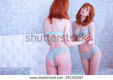 Portrait of seductive young ginger woman looking into the mirror