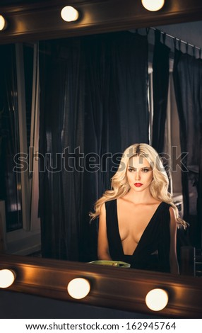 Portrait of seductive young girl looking into mirror - stock photo