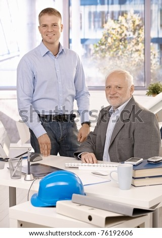 Portrait of senior and junior businessmen working in office, looking at camera, smiling.? - stock photo