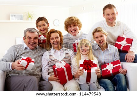 Portrait of senior and young couples and their children with giftboxes - stock photo