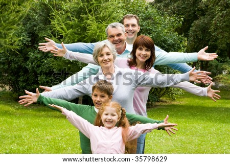 Portrait of senior and young couples with their children having fun outdoors - stock photo
