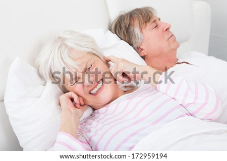 Portrait Of Senior Angry Woman Awaken By Her Husband Snoring - stock photo