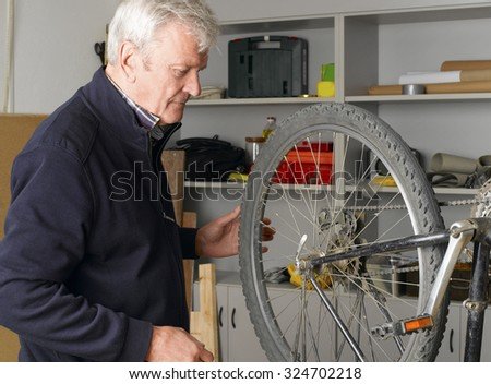 Portrait of senior bike shop owner working in his workshop. Small business.