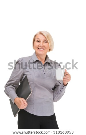Portrait of senior blonde woman standing isolated on white background. Woman wearing grey blouse. Smiling businesswoman looking at camera, holding laptop and cup of coffee