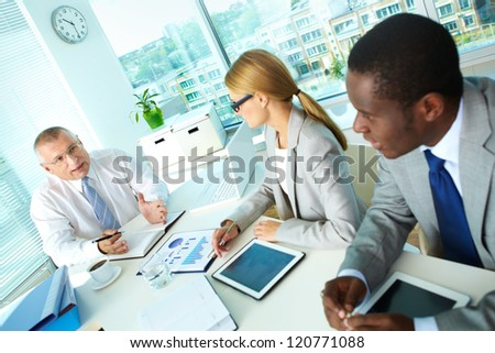 Portrait of senior boss and his employees discussing new project at meeting - stock photo