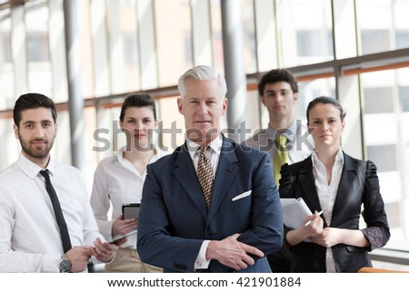 portrait of senior businessman as leader  at modern bright office interior, young  people group in background as team - stock photo
