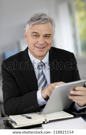 Portrait of senior businessman in office using tablet