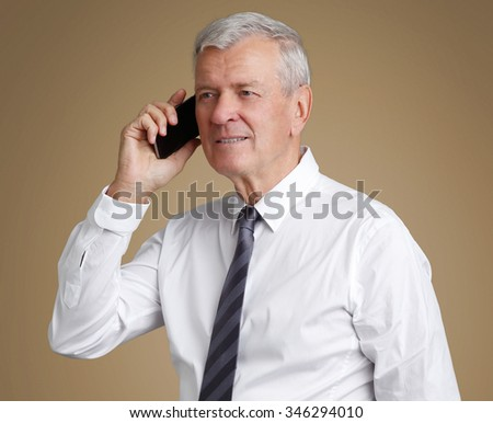 Portrait of senior businessman making call while standing at isolated background.