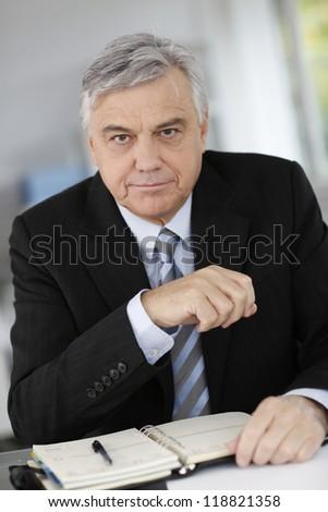 Portrait of senior businessman sitting at desk - stock photo