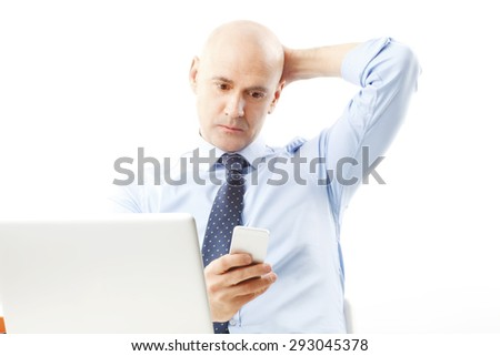 Portrait of senior businessman sitting at desk in front of laptop. Business people holding hand his mobile and reading email. Isolated on white background.