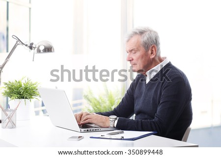 Portrait of senior businessman sitting at office in front of laptop and working on his presentation.