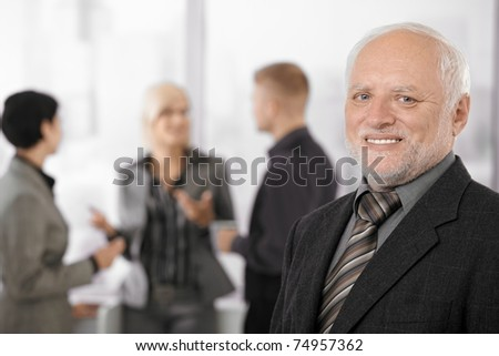 Portrait of senior businessman smiling at camera, team discussing work in background.? - stock photo