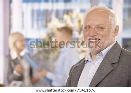 Portrait of senior businessman smiling in office, colleagues in background.? - stock photo