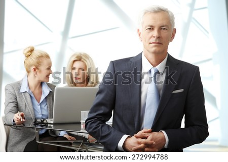 Portrait of senior businessman standing at office while businesswomen standing at background in front of laptop. Group of business people. - stock photo