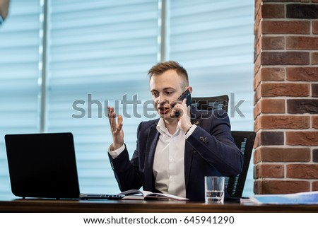 Portrait of senior businessman talking on a mobile phone in office