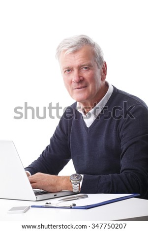 Portrait of senior businessman working on laptop while sitting at office desk. Isolated on white background.