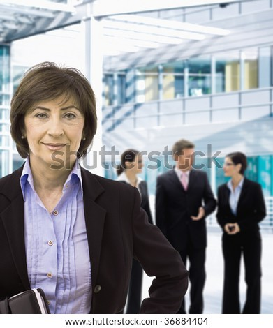 Portrait of senior businesswoman standing in corporate office lobby, smiling. - stock photo
